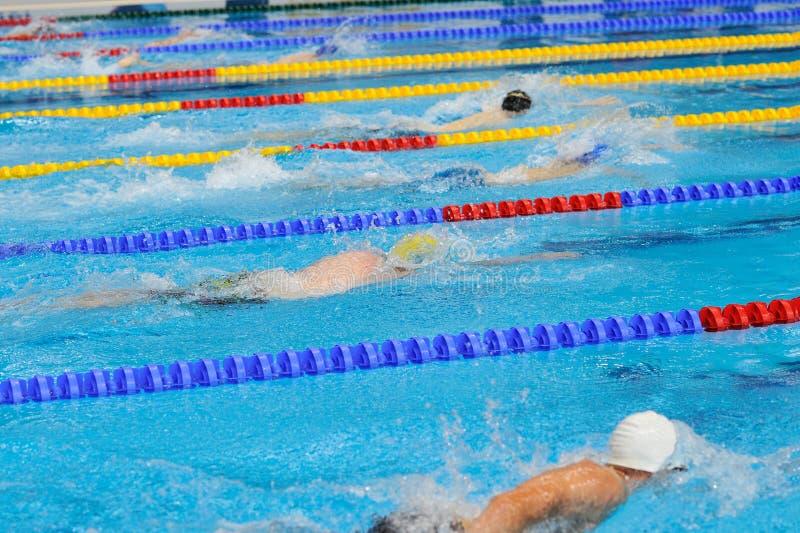 Nadar: Os atletas novos estão nadando no curso de borboleta na fotografia de stock