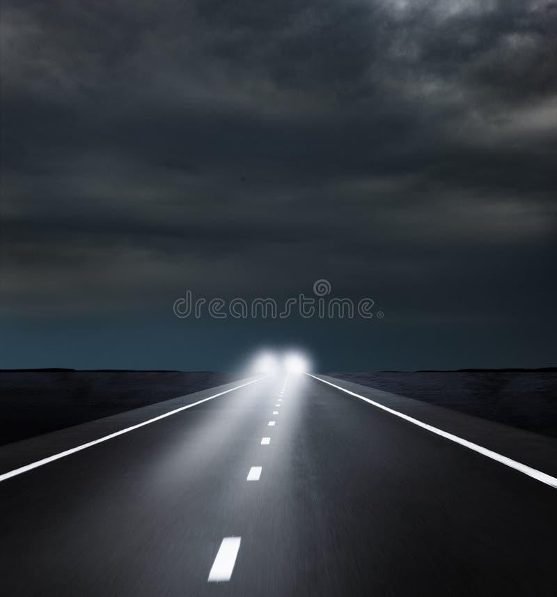 Nadchodzący reflektory na Ciemnej drodze fotografia stock