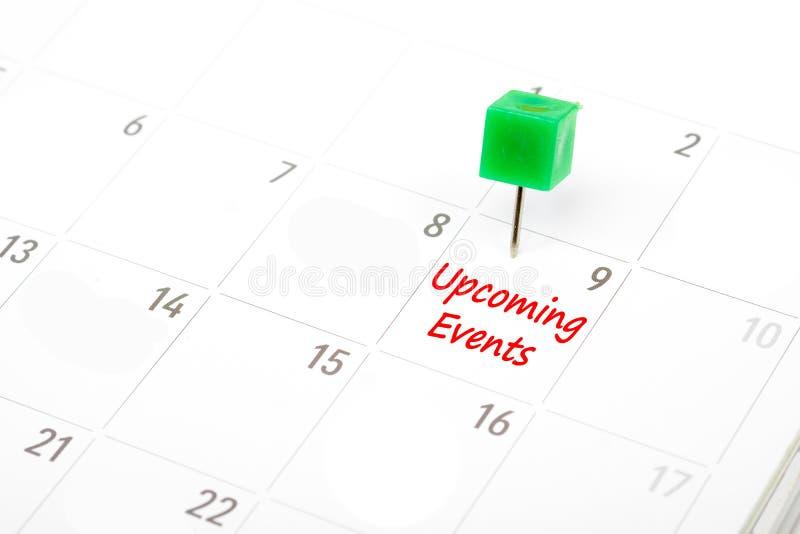 Nadchodzący wydarzenia pisać na kalendarzu z zieloną pchnięcie szpilką r obraz royalty free