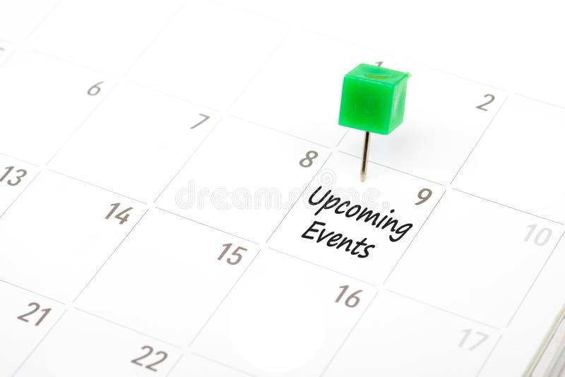Nadchodzący wydarzenia pisać na kalendarzu z zieloną pchnięcie szpilką r obrazy stock