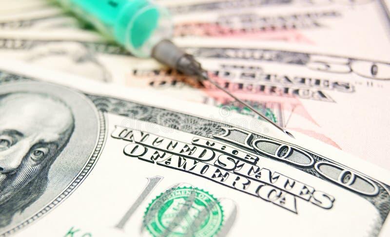 Nadel, Spritze auf Geld. stockfoto