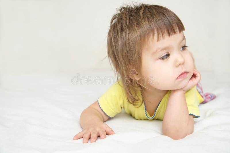 Nadenkend kind, denkend Meisje die op bed liggen die awa kijken stock fotografie