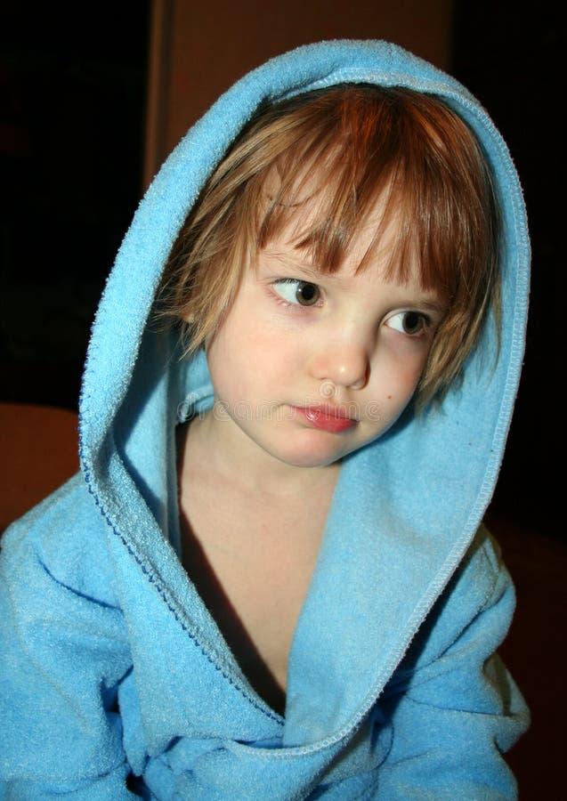Nadenkend meisje in blauwe badjas met kap stock foto's