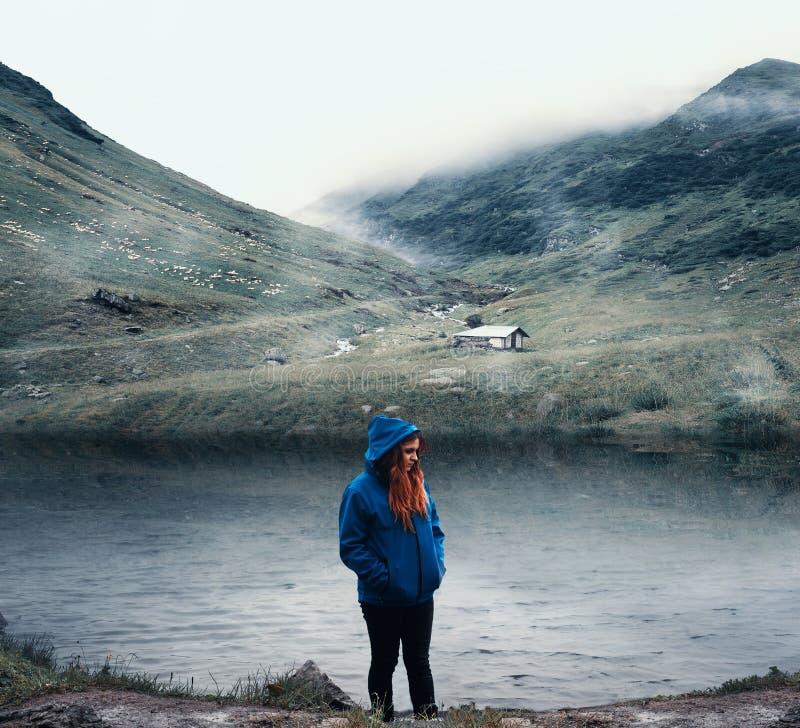 Nadenkend meisje die zich dichtbij het bergmeer bevinden royalty-vrije stock foto's