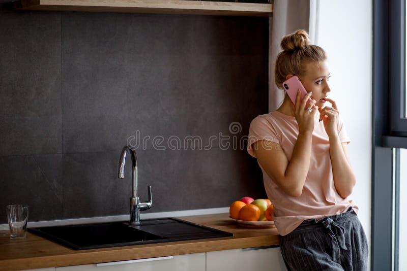 Nadenkend meisje met een vinger op lippen die opzij terwijl status in de keuken eruit zien royalty-vrije stock afbeelding