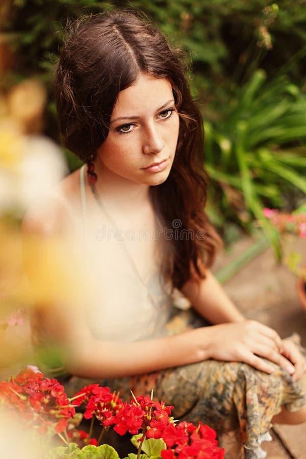 Nadenkend meisje met geraniums stock fotografie