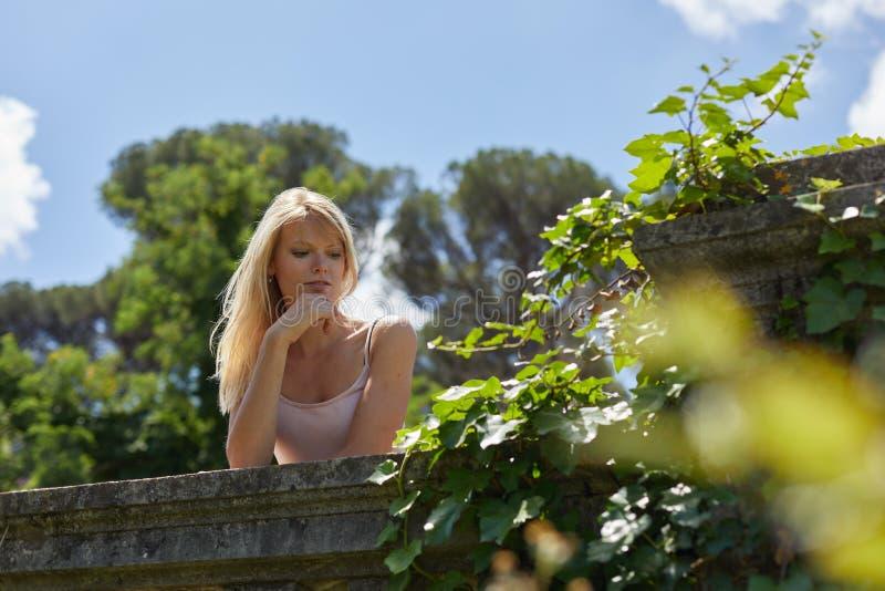 Nadenkend meisje over een dagdromen van het balkonpark royalty-vrije stock foto's
