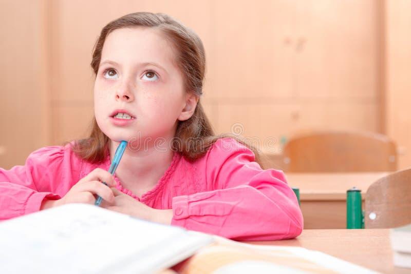Nadenkend meisje tijdens klassen stock foto