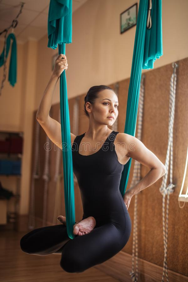 Nadenkend schitterend geschikt meisje met flexibele benen die in de hangmat rusten royalty-vrije stock afbeelding