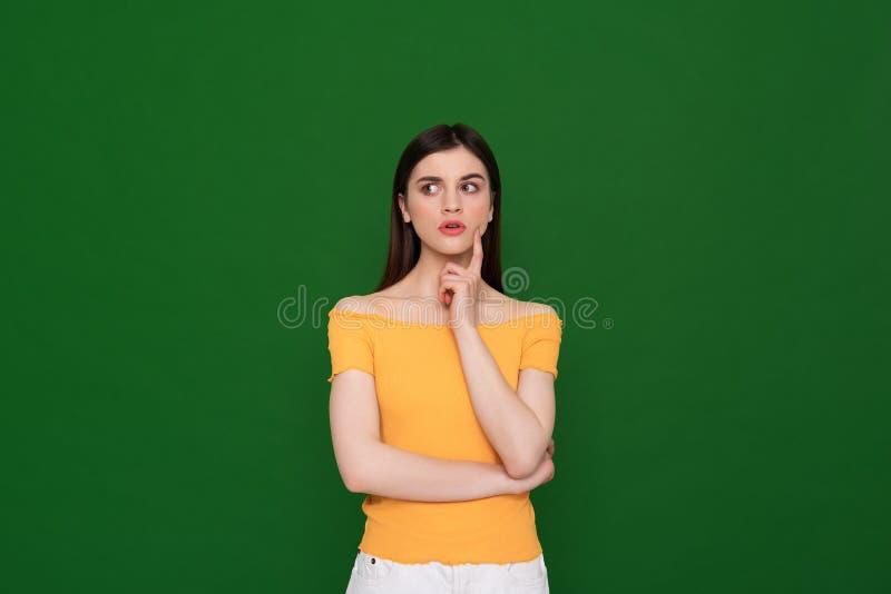 Nadenkend vrij jong meisje dat op groen wordt ge?soleerd royalty-vrije stock afbeeldingen