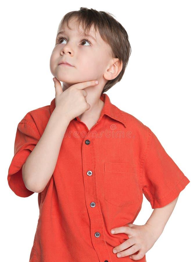 Nadenkend weinig jongen in een rood overhemd stock foto's
