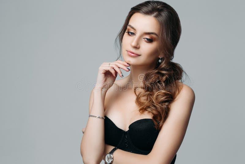 Nadenkende aantrekkelijke modieuze jonge die vrouw op grijze achtergrond wordt geïsoleerd royalty-vrije stock foto