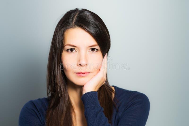 Nadenkende aantrekkelijke vrouw met een rustig gezicht royalty-vrije stock fotografie