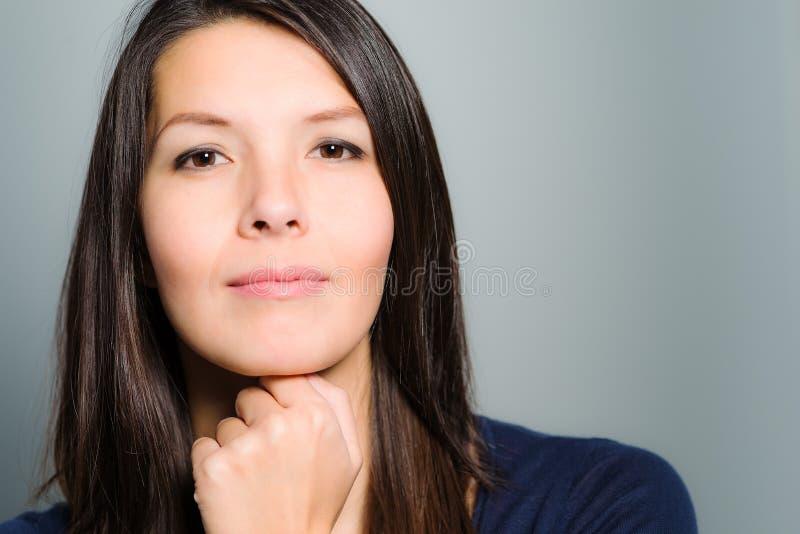 Nadenkende aantrekkelijke vrouw met een rustig gezicht royalty-vrije stock afbeelding