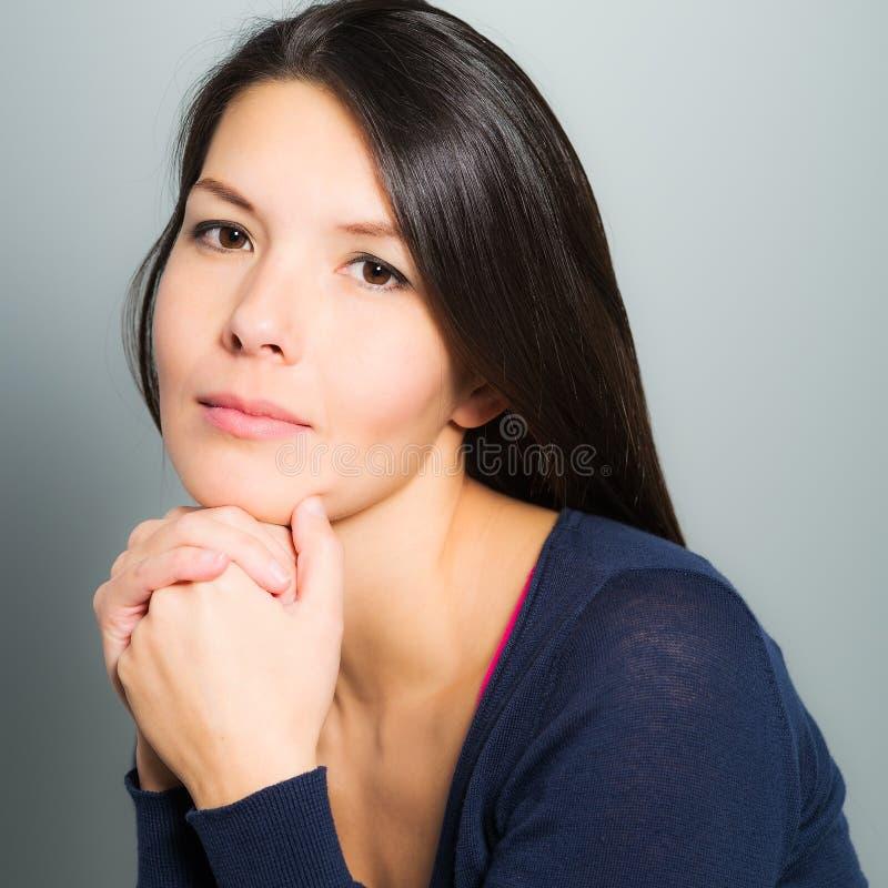 Nadenkende aantrekkelijke vrouw met een rustig gezicht stock afbeelding