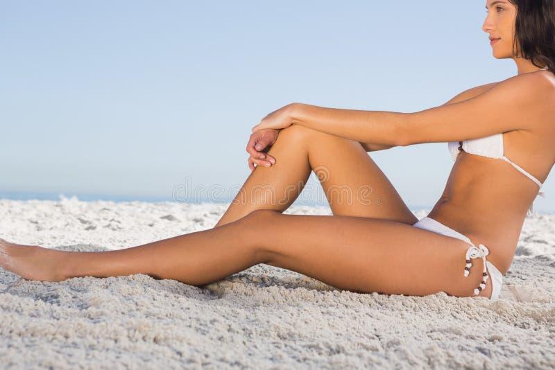 Nadenkende aantrekkelijke vrouw in witte bikini die terwijl het zitten stellen stock afbeeldingen