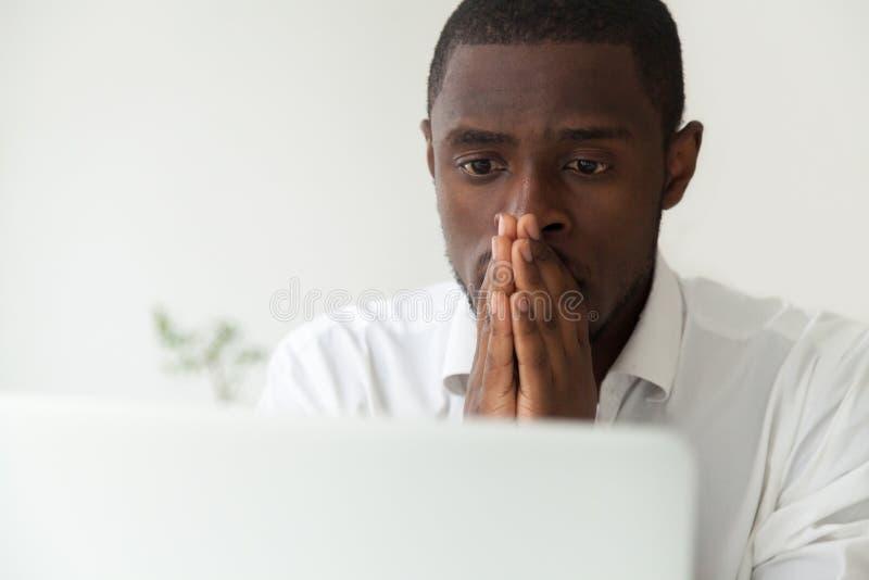 Nadenkende Afrikaanse Amerikaanse arbeider die voor computerbegin ope hopen stock afbeelding