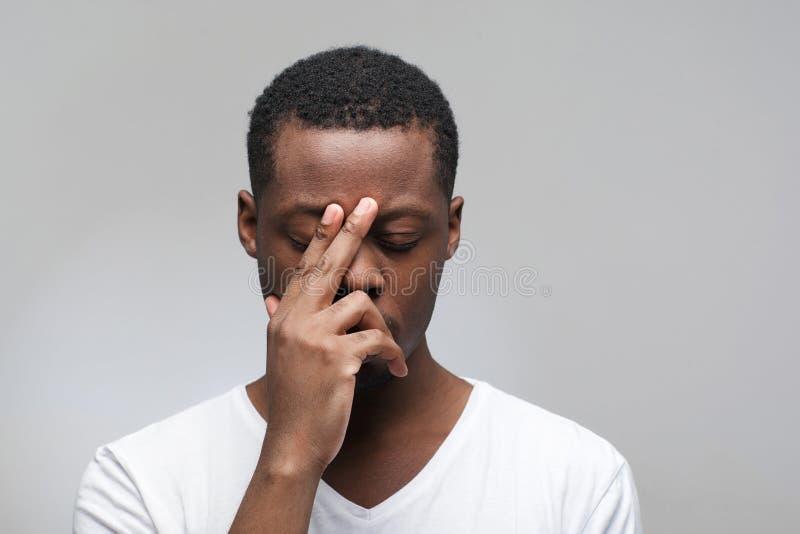 Nadenkende Afrikaanse Amerikaanse jonge gesloten kerelogen royalty-vrije stock foto