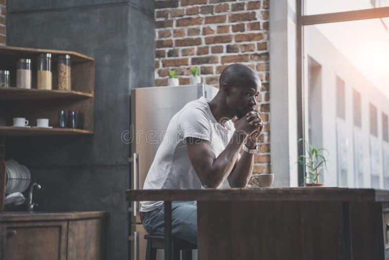 nadenkende Afrikaanse Amerikaanse mens die zijn ochtendkoffie hebben stock foto's