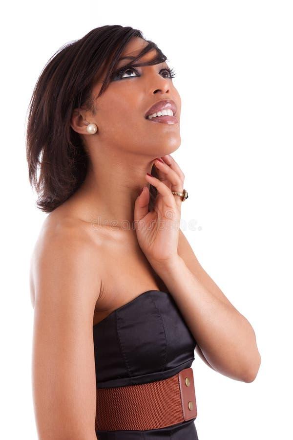 Nadenkende Afrikaanse vrouw met elegante zwarte kleding stock afbeelding