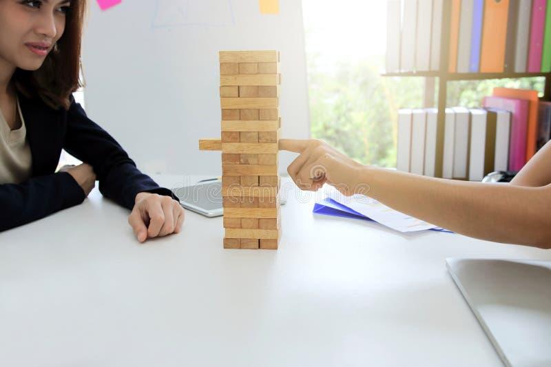 Nadenkende en bedachtzame groep bedrijfsmensen die houten bloktoren of jenga in bureau spelen Risico en strategie bedrijfsconcept royalty-vrije stock foto's