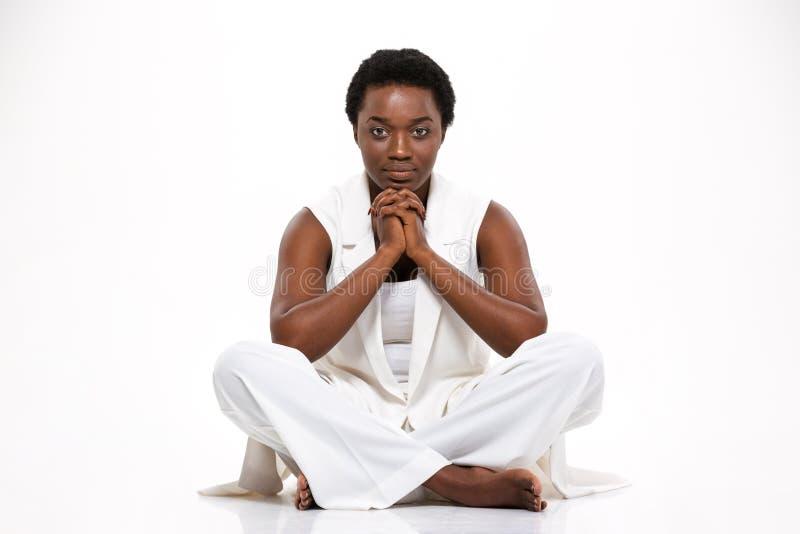 Nadenkende ernstige Afrikaanse Amerikaanse jonge vrouwenzitting met gekruiste benen royalty-vrije stock foto