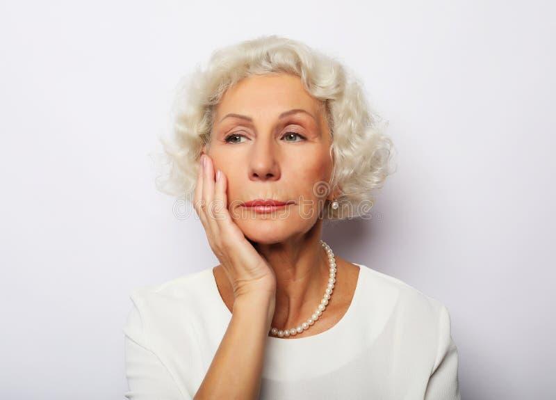 Nadenkende ernstige hogere vrouw die blauw voelen ongerust gemaakt over problemen royalty-vrije stock foto