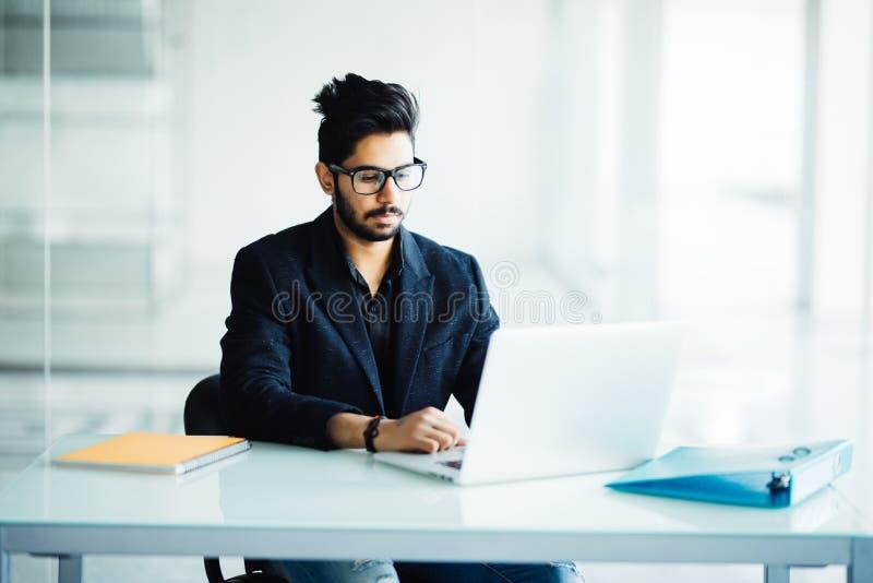 Nadenkende geconcentreerde jonge internationale mannelijke studenten die concept planning voor coursework maken die aan het uitbr royalty-vrije stock foto's