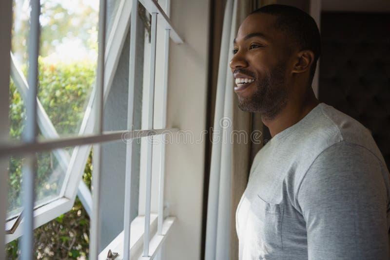 Nadenkende glimlachende mens die uit door venster thuis kijken stock afbeeldingen
