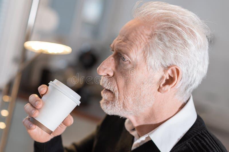 Nadenkende hogere mens tijdens koffiepauze stock foto