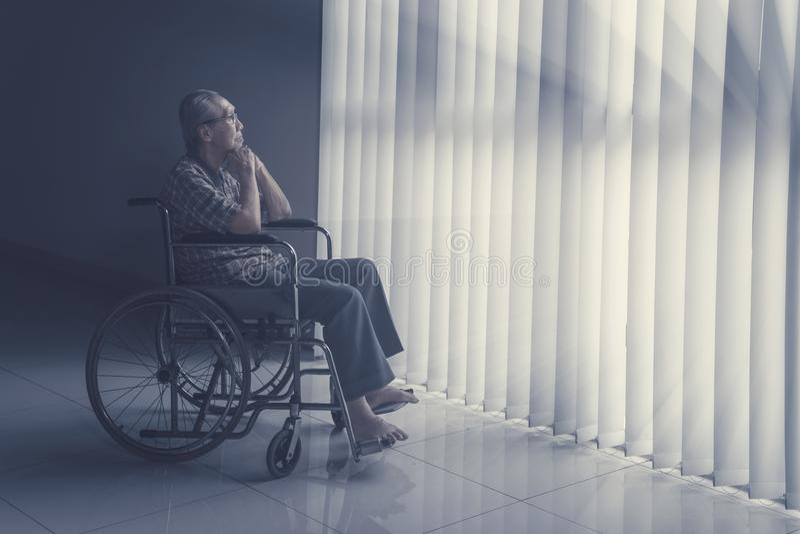 Nadenkende hogere mensenzitting op rolstoel royalty-vrije stock afbeelding