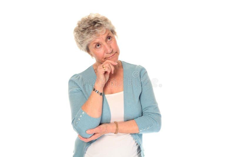Nadenkende hogere oudere vrouw stock fotografie