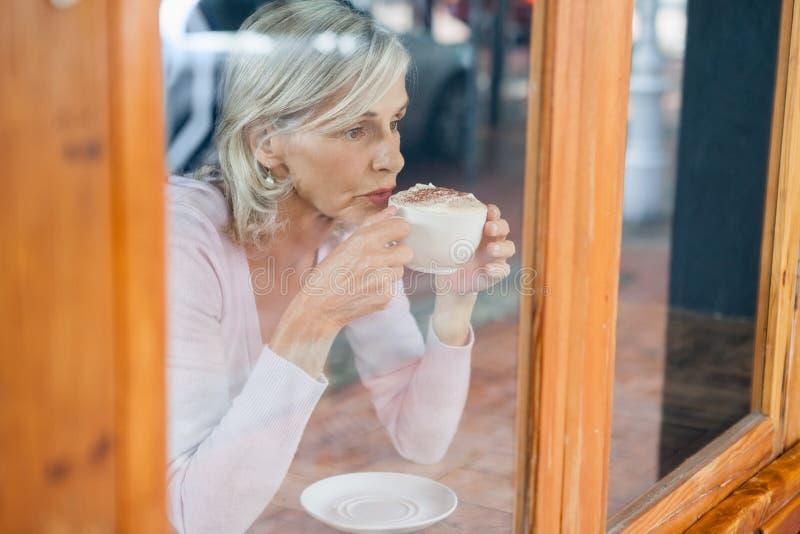 Nadenkende hogere vrouw het drinken koffie terwijl het zitten door lijst royalty-vrije stock afbeeldingen