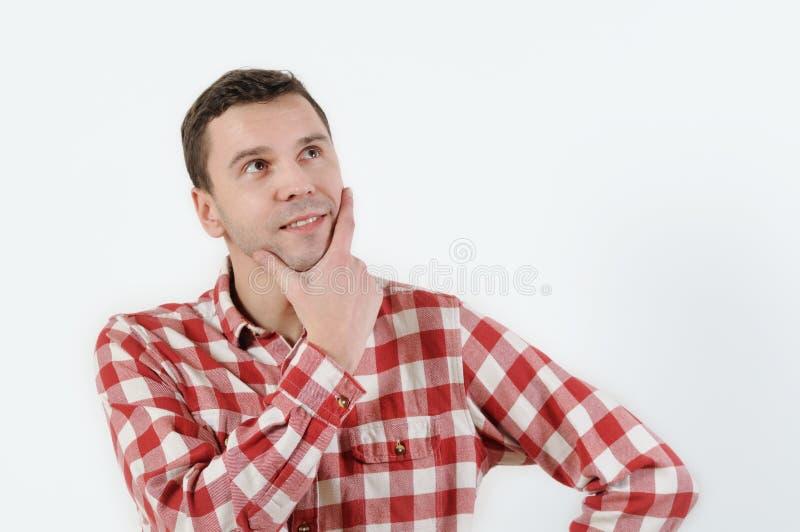 Nadenkende jonge mens in de holdingshand van het hipsteroverhemd op kin en status tegen witte achtergrond stock foto