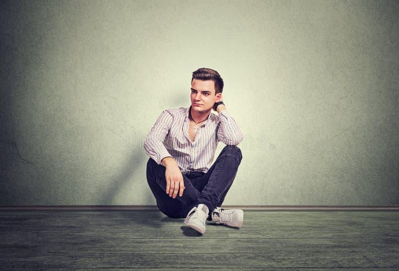 Nadenkende jonge mens het denken zitting op een grijze vloer stock foto