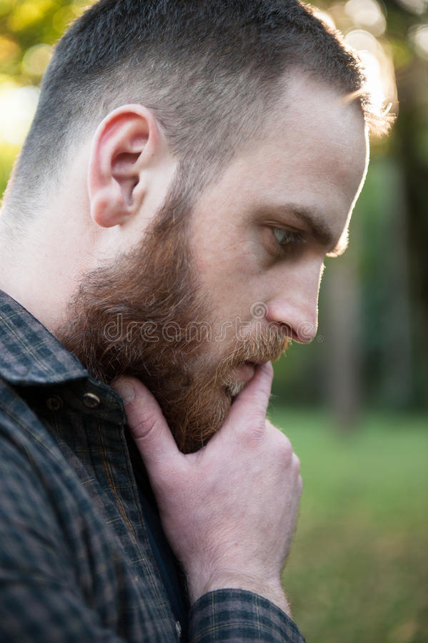 Nadenkende jonge mens met een baard stock afbeelding