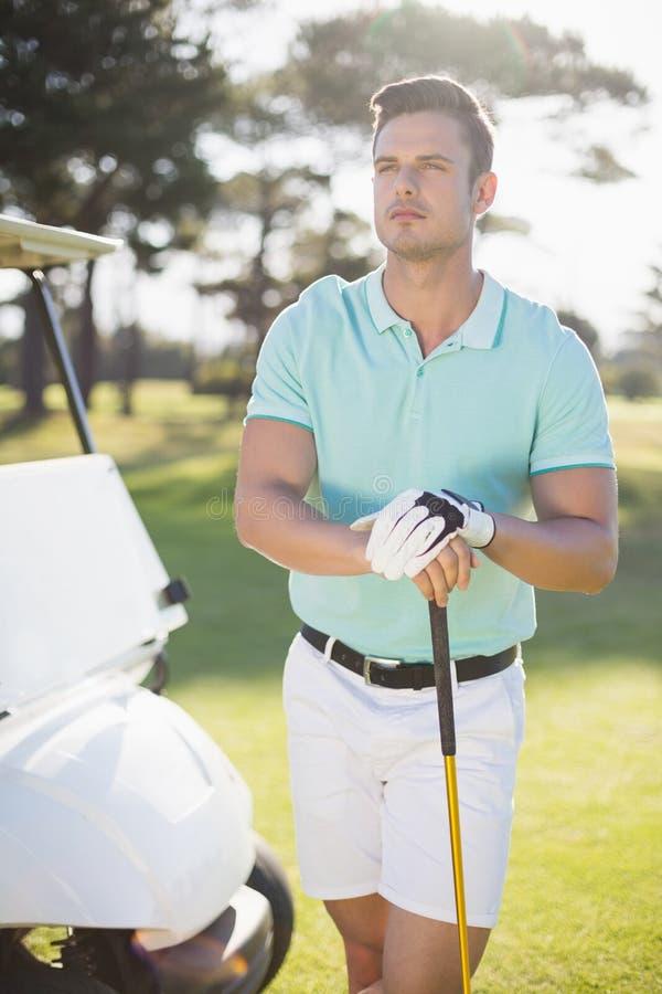 Nadenkende jonge mens met golfclub stock foto