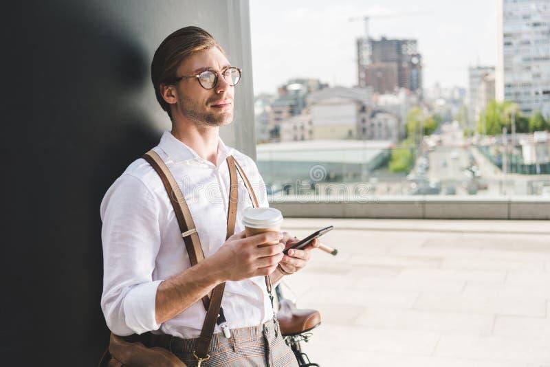 nadenkende jonge mens met koffie gaan gebruikend smartphone stock afbeeldingen