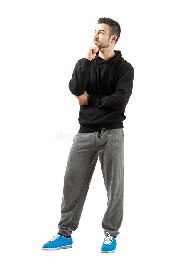 Nadenkende jonge mens in sportkleding stock afbeelding