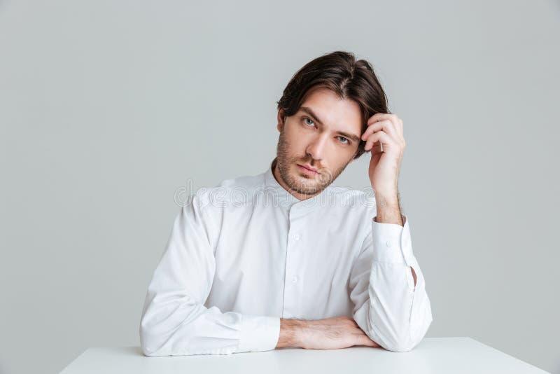 Nadenkende jonge mens in witte overhemdszitting bij de lijst royalty-vrije stock foto's