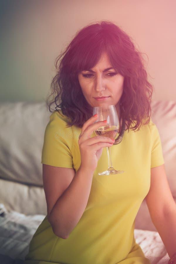 Nadenkende jonge vrouw die een glas wijn achterin ruiken, de ochtend royalty-vrije stock foto