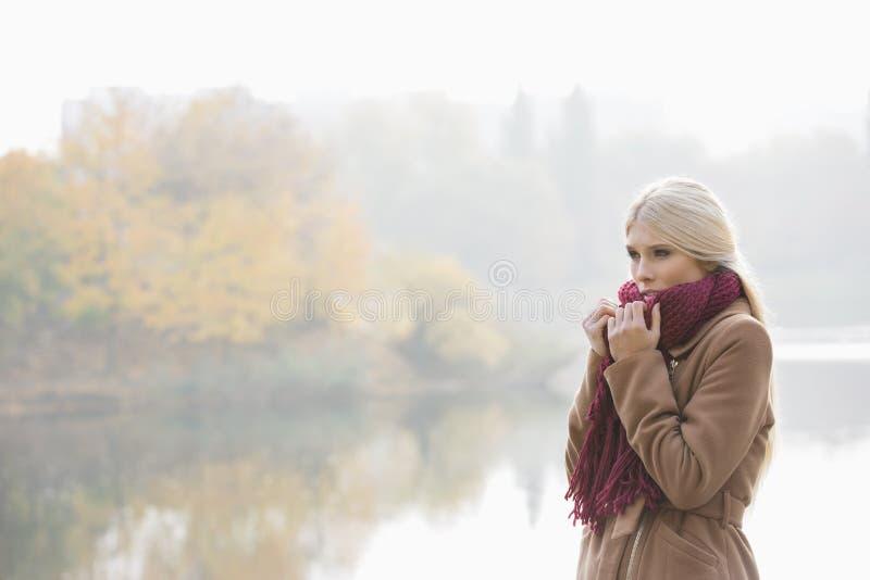 Nadenkende jonge vrouw die geluiddemper dragen bij oever van het meer in park royalty-vrije stock afbeeldingen