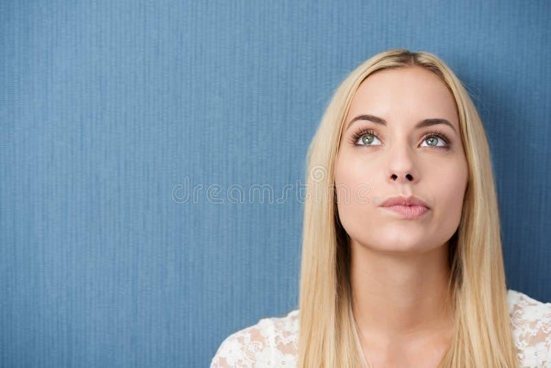 Nadenkende jonge vrouw die haar lip bijten royalty-vrije stock afbeeldingen