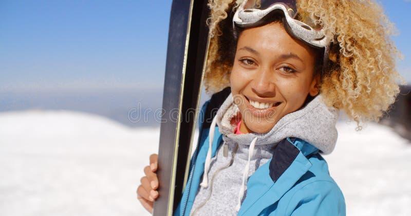 Nadenkende jonge vrouw die houdend haar skis bevinden zich royalty-vrije stock afbeelding