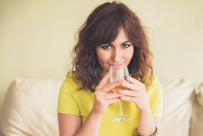 Nadenkende jonge vrouw die witte wijn drinken stock fotografie