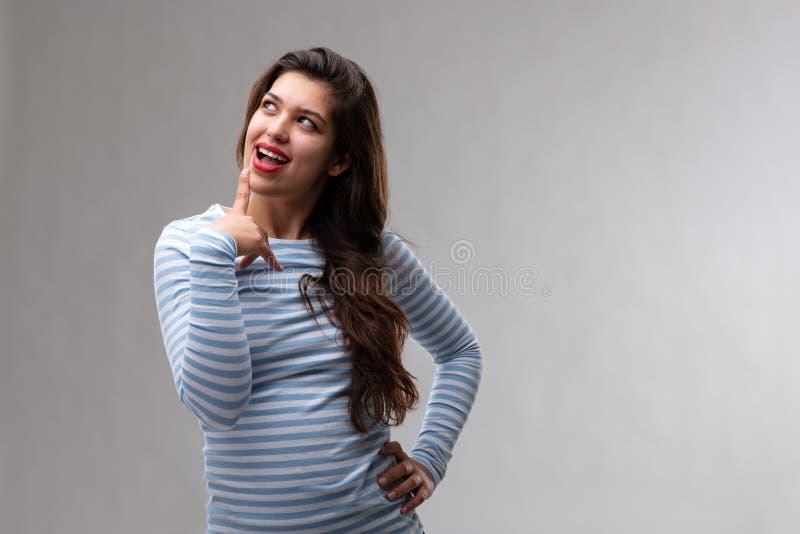Nadenkende jonge vrouw met een blik van anticiperen stock afbeelding