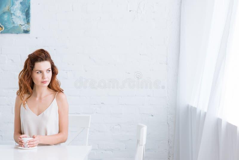 nadenkende jonge vrouw met kop van koffie voor het witte bakstenen muur kijken stock afbeelding