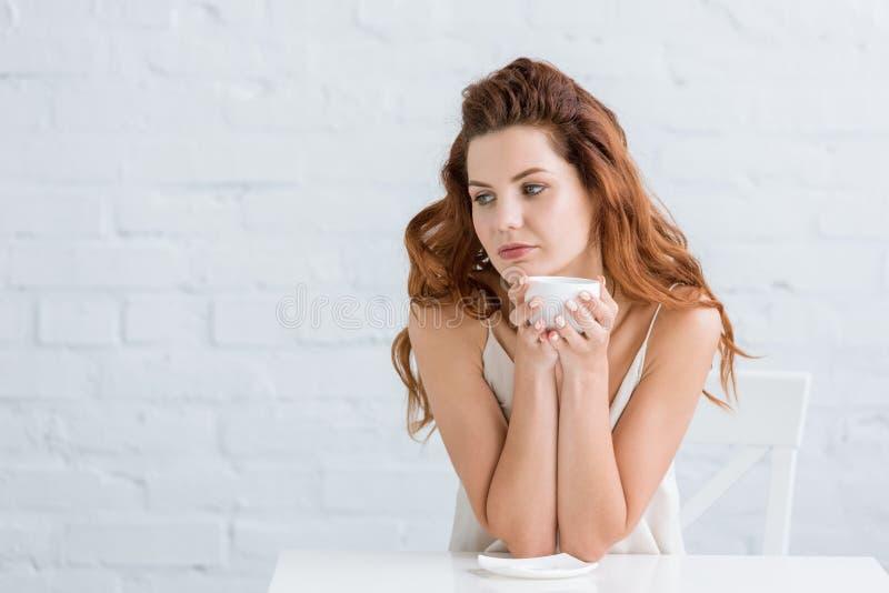 nadenkende jonge vrouw met kop van koffie voor wit royalty-vrije stock fotografie