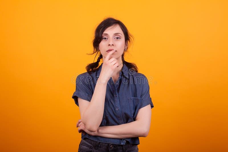 Nadenkende jonge vrouw in studio met hand dichtbij het gezicht over gele achtergrond royalty-vrije stock afbeeldingen