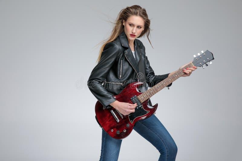 Nadenkende jonge vrouwen die elektrische gitaar spelen stock foto